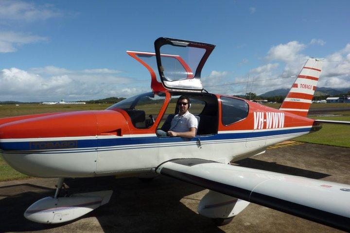 L'auteur posant dans un avion Tobago rouge et blanc , dont l'immatriculation est VH-WWW